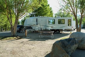 Fifth wheel RV in large RV site with picnic table