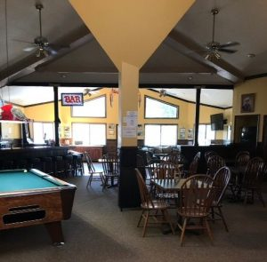 Inside bar with yellow walls pool table and table and chairs